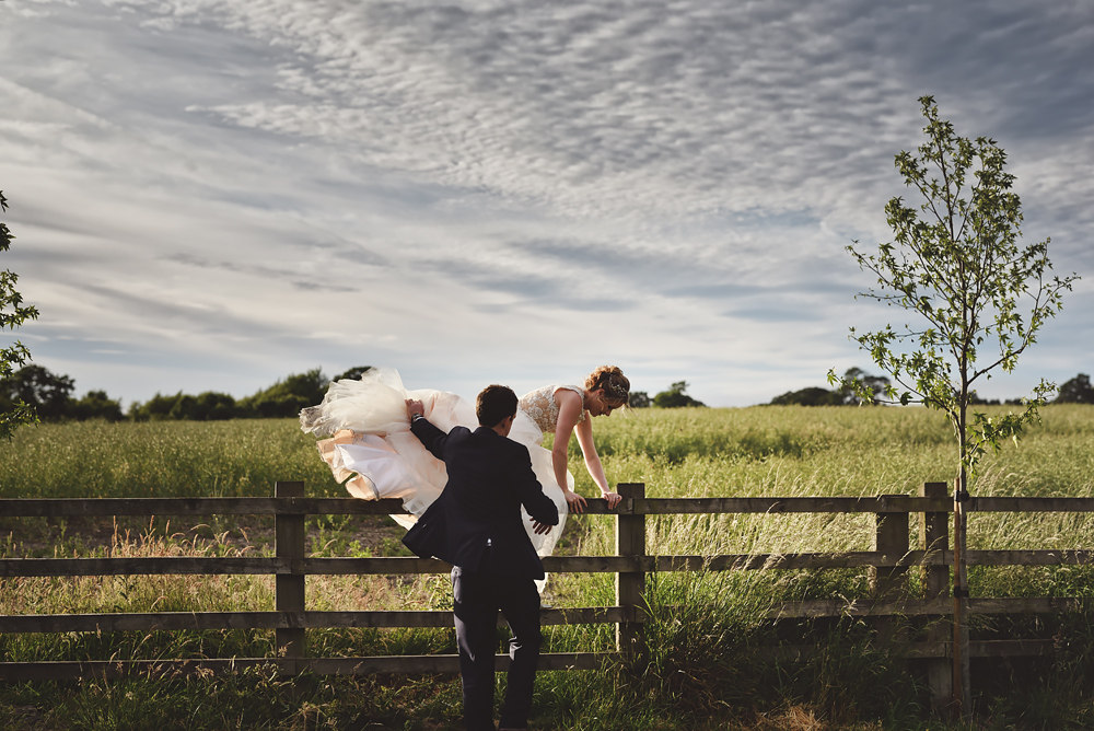 Bride climbing over a fence - Sandhole Oak Barn Wedding