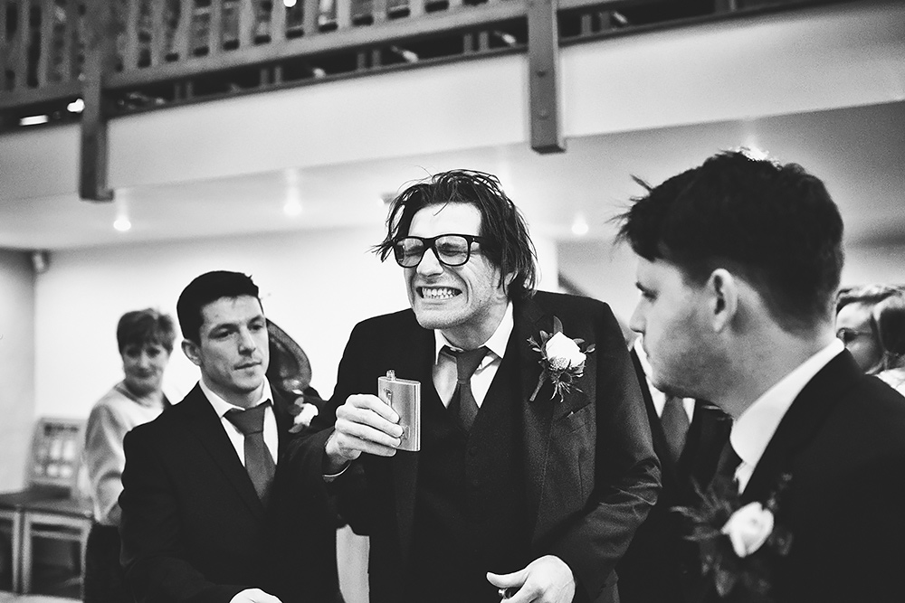Usher drinking from hip flask - wedding